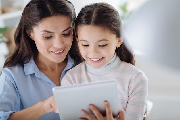 Nowoczesne urządzenie. zachwycona pozytywna śliczna dziewczyna uśmiecha się i patrzy na stół, siedząc razem z matką