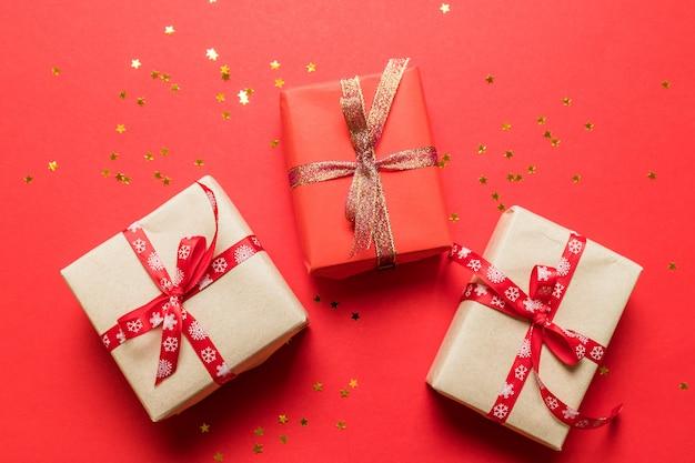 Nowoczesne w wielokolorowych papierowych pudełkach niespodzianki ze złotymi błyszczącymi wstążkami na czerwonym tle. może służyć do urodzinowego banera, zdjęcia do artykułu, urodzinowego plakatu lub kartki pocztowej.