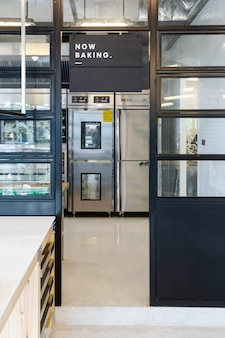 Nowoczesne wejście do kuchni cukierniczej z płytką now baking utrzymaną w czarno-białej stali.