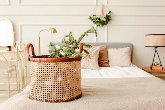 Nowoczesne wnętrza sypialni w stylu skandynawskim z koszem na wieniec z gałązkami jodły
