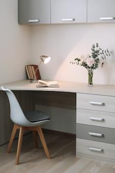 Nowoczesne wnętrze domu. drewniane biurko z książkami i kwiatami. koncepcja planowania i projektowania. miejsce pracy. kobiecy płaski leżak.