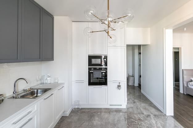 Nowoczesne wnętrze jasnej kuchni w mieszkaniu ze stołem jadalnym i sprzętem w zabudowie