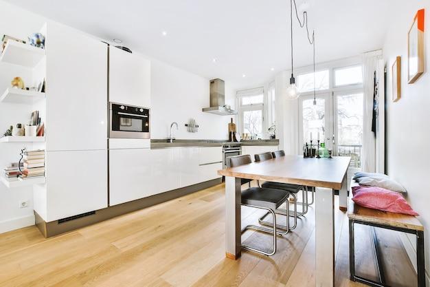 Nowoczesne wnętrze jednoliniowej kuchni z białymi błyszczącymi szafkami i chromowanym urządzeniem w pokoju z panoramicznymi oknami