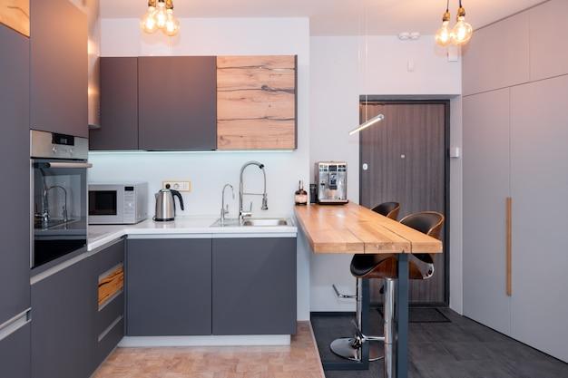 Nowoczesne wnętrze kuchni z oświetleniem na brązowym drewnianym stole i stołkach barowych, ekspres do kawy. współczesne wnętrze z elementami loftu