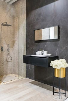 Nowoczesne wnętrze łazienki z białymi ścianami, kabiną prysznicową ze szklaną ścianą, umywalką i toaletą