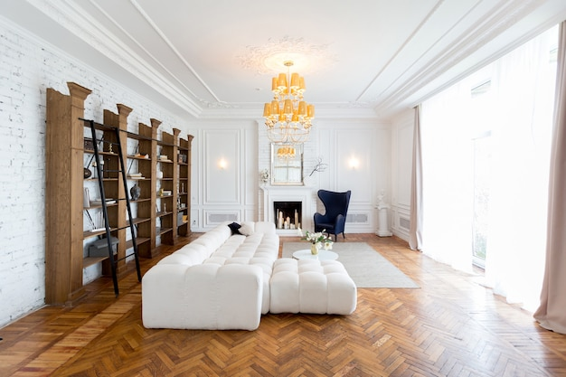 Nowoczesne wnętrze luksusowego dużego jasnego salonu. biała droga kanapa i drewniane półki, białe ściany z listwami i luksusowy żyrandol