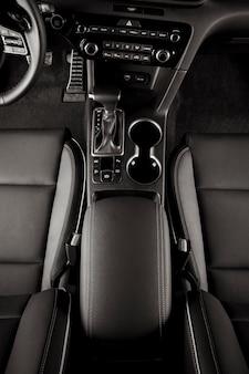 Nowoczesne wnętrze nowego samochodu, sportowa kierownica, dźwignia automatycznej skrzyni biegów, widok z góry