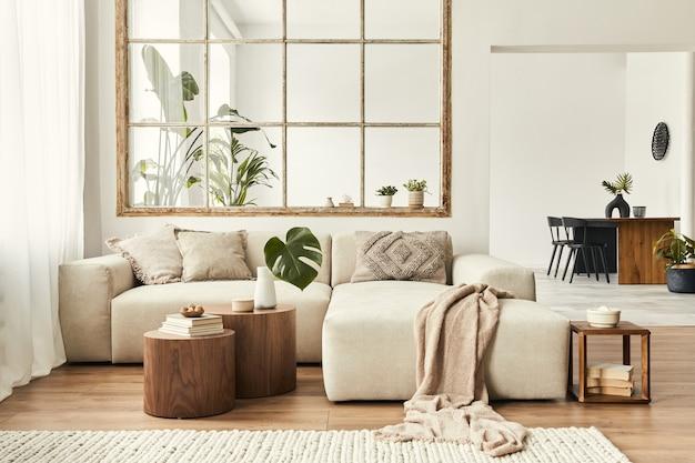 Nowoczesne wnętrze open space z designerską sofą modułową, meblami, drewnianymi stolikami kawowymi, pledami, poduszkami, tropikalnymi roślinami i eleganckimi dodatkami osobistymi w stylowym wystroju domu. salon neutralny.