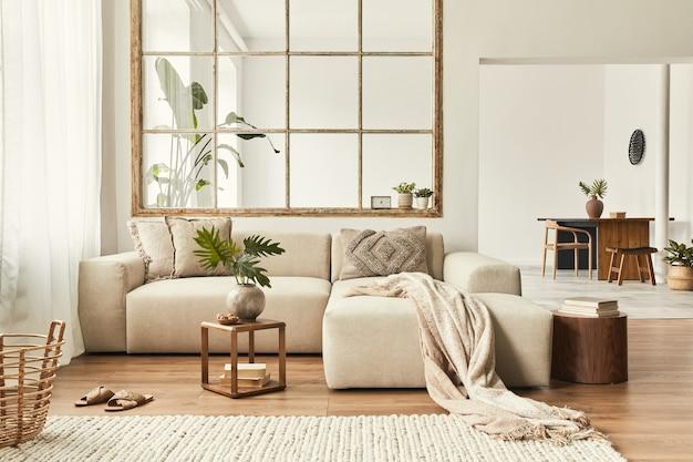 Nowoczesne wnętrze otwartej przestrzeni z designerską sofą modułową, meblami, drewnianymi stolikami kawowymi, pledami, poduszkami, tropikalnymi roślinami i eleganckimi dodatkami osobistymi w stylowym wystroju domu. neutralny salon.