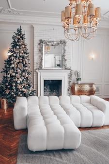 Nowoczesne wnętrze salonu w kolorze białym z klasycznymi elementami i choinką