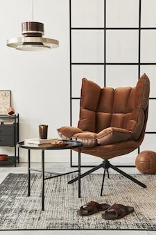 Nowoczesne wnętrze salonu z designerskim brązowym fotelem, stolikiem bocznym, lampą wiszącą, ścianą loftową, kapciami, dywanem, dekoracją i eleganckimi akcesoriami osobistymi w wystroju domu.