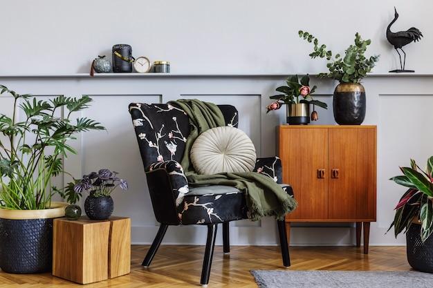 Nowoczesne wnętrze salonu z designerskim fotelem, drewnianą komodą vintage, boazerią z półką, mnóstwem roślin, kostką, dywanem, szarą ścianą i osobistymi dodatkami w wystroju domu.
