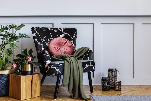 Nowoczesne wnętrze salonu z designerskimi fotelami, boazerią z półką, mnóstwem roślin, stolikiem kawowym, szarą ścianą, decpration, dywanem i akcesoriami osobistymi w wystroju domu.
