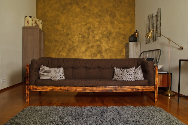 Nowoczesne wnętrze salonu z teksturowaną złotą ścianą, brązową drewnianą stylową sofą i meblami domowymi