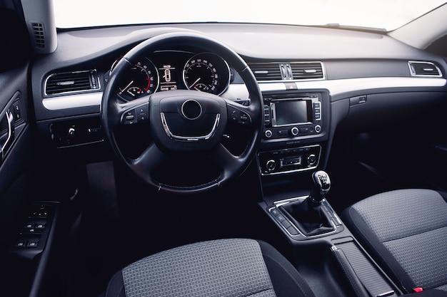 Nowoczesne wnętrze samochodu, kierownica, dźwignia zmiany biegów, system multimedialny i deska rozdzielcza.