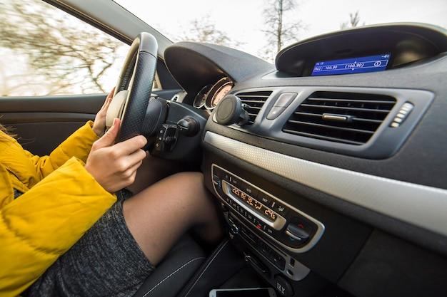 Nowoczesne wnętrze samochodu z kobiecych rąk kierowcy na kierownicy. koncepcja bezpiecznej jazdy.