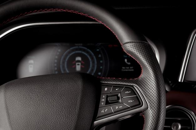 Nowoczesne wnętrze samochodu z nową technologią, skórzaną kierownicą i cyfrowym wyświetlaczem prędkościomierza