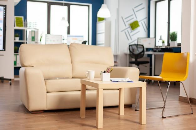 Nowoczesne wnętrze strefy relaksu biznesowego z wygodną kanapą i pomarańczowym krzesłem