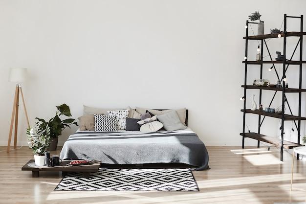 Nowoczesne wnętrze sypialni z kolorowym łóżkiem, dywanem z geometrycznym wzorem i małym drewnianym stolikiem kawowym