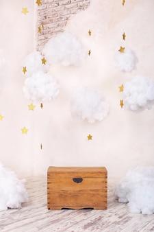 Nowoczesne wnętrze vintage pokoju dziecięcego ze starą drewnianą skrzynią na teksturowanej ścianie z chmurami. wnętrze placu zabaw dla dzieci. skrzynia na zabawki i gry dla dzieci. wystrój pokoju dziecięcego