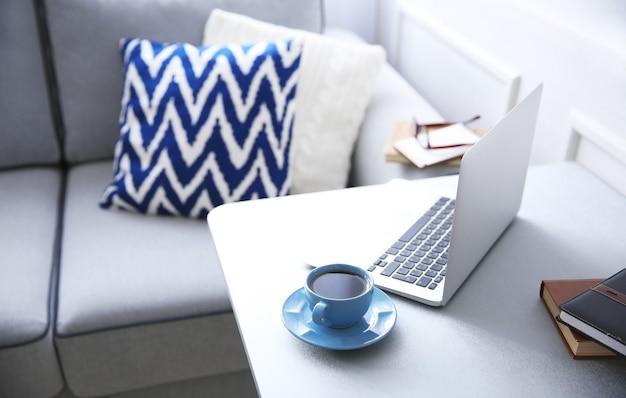 Nowoczesne wnętrze. wygodne miejsce pracy. stół z laptopem i filiżanką kawy na nim
