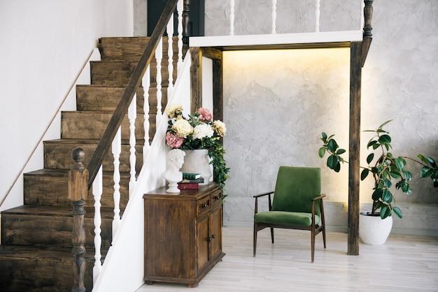 Nowoczesne wnętrze z drewnianymi schodami i krzesłami wypoczynkowymi