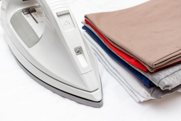 Nowoczesne żelazko elektryczne i stos kolorowych ubrań na białym tle