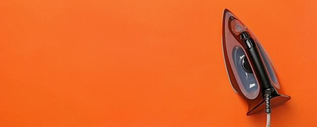 Nowoczesne żelazko na pomarańczowym tle, miejsce na tekst