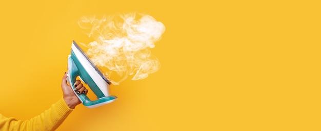 Nowoczesne żelazko z parą w ręku na żółtym tle, panoramiczny obraz makiety