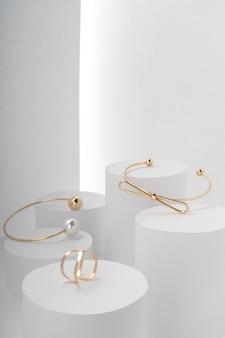 Nowoczesne złote bransoletki i złoty pierścionek na białych okrągłych platformach
