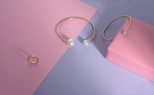Nowoczesne złote bransoletki z perłami i diamentami na różowym i fioletowym tle papieru