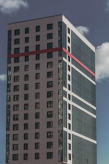 Nowoczesny apartamentowiec w szaro-czerwonym budynku.