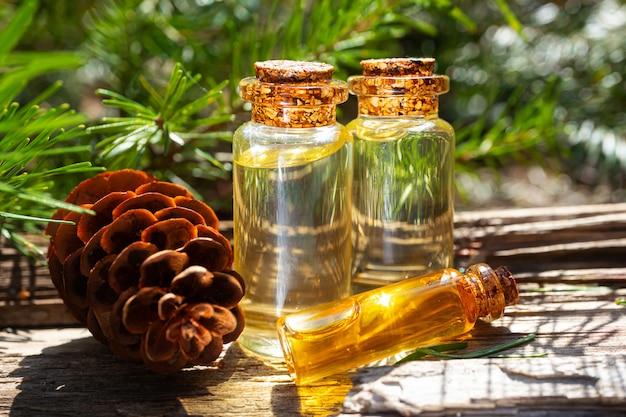 Nowoczesny aptekarz. naturalny olej świerkowy na drewnianej powierzchni w lesie wśród jodeł.