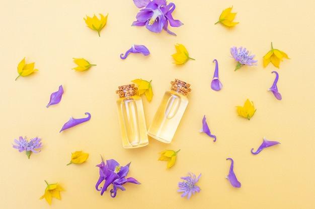 Nowoczesny aptekarz. olejek eteryczny wśród kwiatów i płatków. obraz w odcieniach żółtego i fioletu.