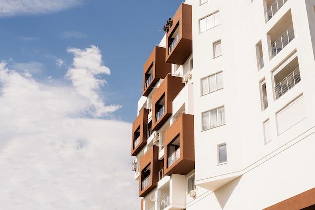 Nowoczesny biało-brązowy hotel lub budynek mieszkalny na tle nieba
