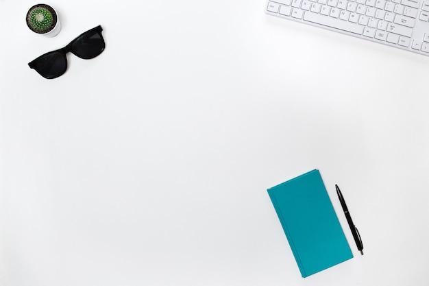Nowoczesny biały stół biurkowy blogera z białą klawiaturą, okularami przeciwsłonecznymi, kaktusem i pamiętnikiem miętowym