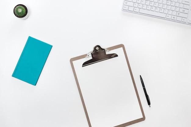 Nowoczesny biały stół biurkowy blogera z białą klawiaturą, składanym tabletem, kaktusem i pamiętnikiem