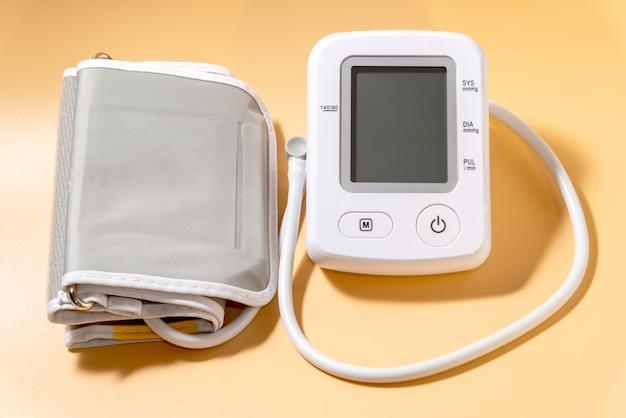 Nowoczesny biały tonometr elektryczny na zbliżenie jasnopomarańczowe tło. urządzenie do pomiaru ciśnienia.