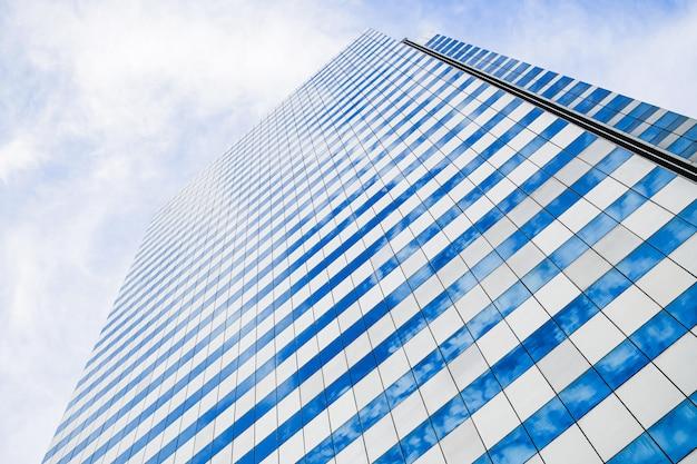 Nowoczesny biurowiec z przeszklonymi oknami odzwierciedla panoramę.