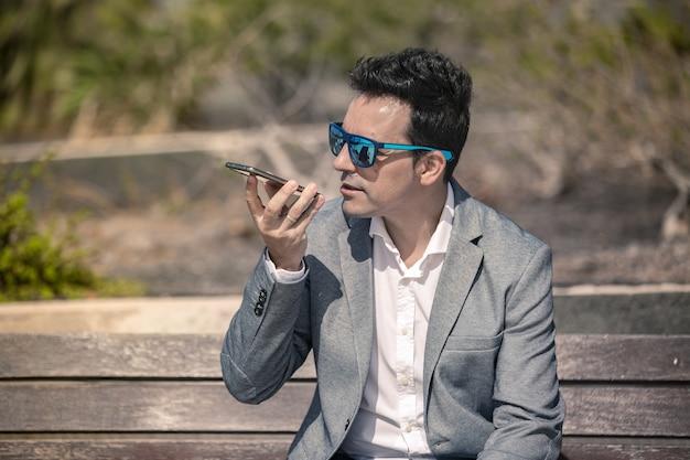 Nowoczesny biznesmen nagrywanie wiadomości głosowej na smartfonie