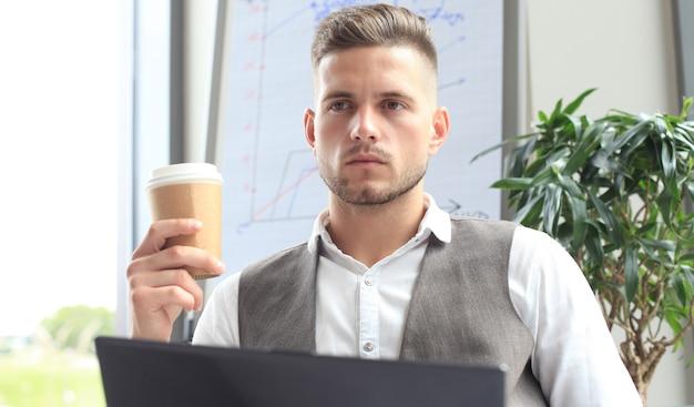 Nowoczesny biznesmen pijący kawę w kawiarni biurowej w porze lunchu i korzystający z laptopa