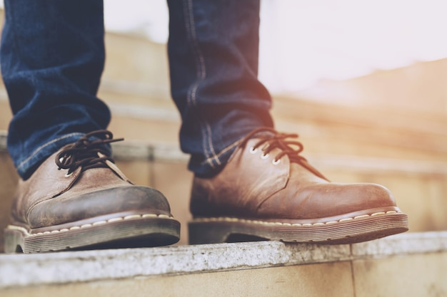 Nowoczesny biznesmen pracujący zbliżenie nogi stoją i chodzą po schodach w nowoczesnym mieście. w godzinach szczytu do pracy w biurze w pośpiechu. pierwszego ranka w pracy. klatka schodowa