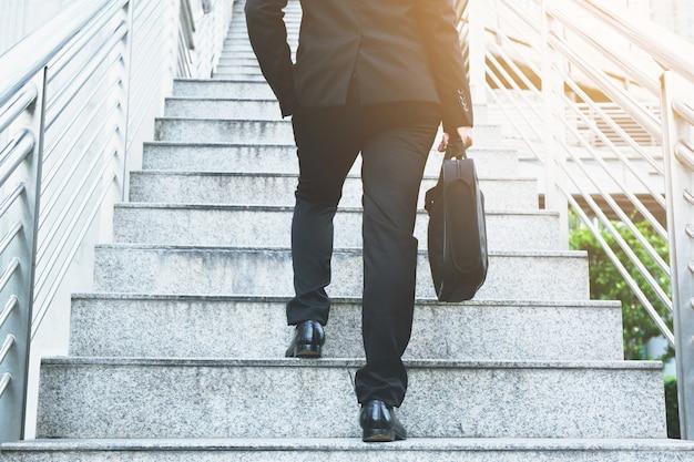 Nowoczesny biznesmen ręka trzyma teczkę obok pracy z bliska nogi chodząc po schodach w nowoczesnym mieście. w godzinach szczytu do pracy w biurze w pośpiechu.