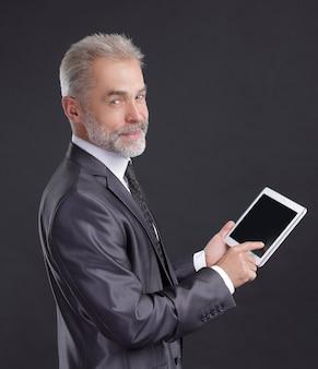 Nowoczesny biznesmen za pomocą cyfrowego tabletu. na białym tle na czarnym tle.