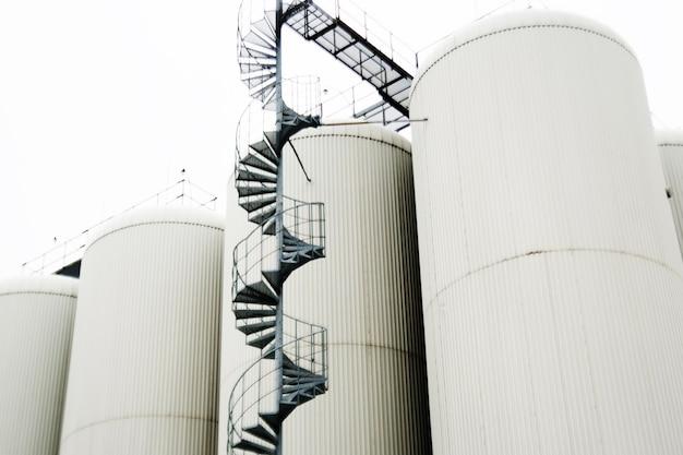 Nowoczesny browar. linie metalowych zbiorników w nowoczesnym browarze. proces technologiczny warzenia piwa. wygląd nowoczesnej fabryki piwa ze zbiornikami piwa ze stali nierdzewnej.