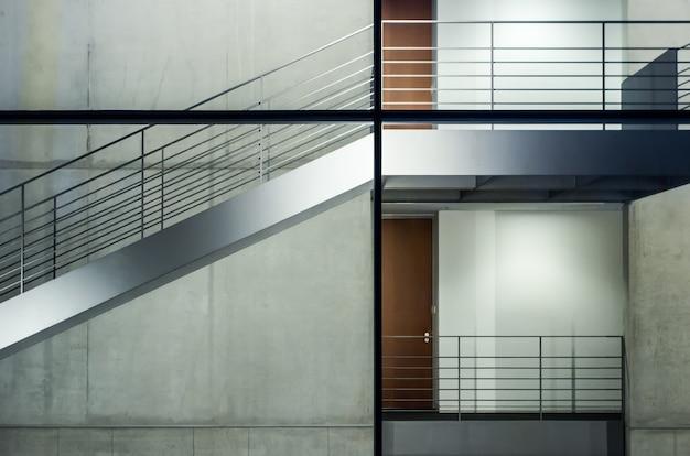 Nowoczesny budynek ze szklanymi oknami i klatkami schodowymi pod światłami