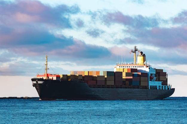 Nowoczesny czarny kontenerowiec wypływający z morza bałtyckiego