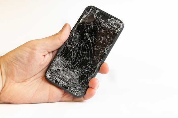 Nowoczesny czarny smartfon z uszkodzonym ekranem w męskiej dłoni na białym tle