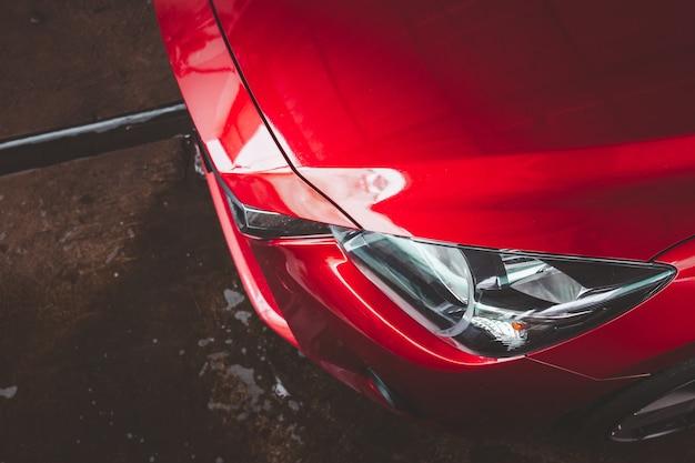 Nowoczesny czerwony samochód z bliska na reflektorach, nowoczesny samochód sedan parking na mokrej podłodze.