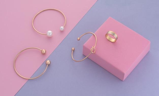 Nowoczesny design złotej biżuterii na różowym pudełku na fioletowym tle